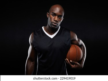 Portrait of confident young man with strong build holding a basket ball against black background. African male athlete looking at camera. Muscular basketball player.