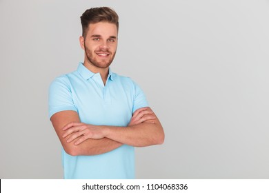 portrait of confident young man wearing light blue polo t-shirt while standing on light grey background with arms folded