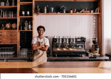 Portrait of confident young man wearing apron standing behind cafe counter. Barista in apron looking at camera and smiling.