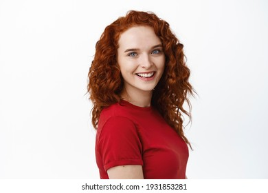Portrait of confident young pretty woman with curly red hair, natural pale skin and light make-up, showing her candid white smile and looking at camera, white background