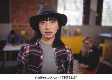 Portrait of confident young woman wearing hat while standing at coffee shop