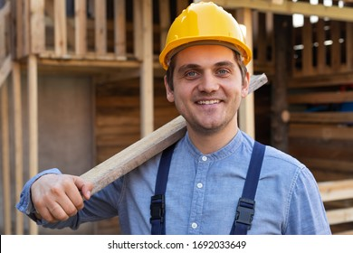 Porträt eines selbstbewussten jungen Arbeitnehmers mit gelbem Helm, blauer Uniform - DIY-Renovierungskonzept