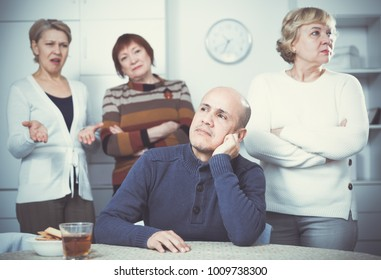 Portrait of conflict mature friends who are displeased at home.