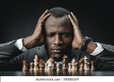 portrait of confused confused african american businessman holding head and looking at chess figures on table isolated on black