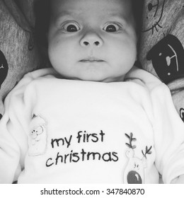 Portrait of a confused baby at his first Christmas