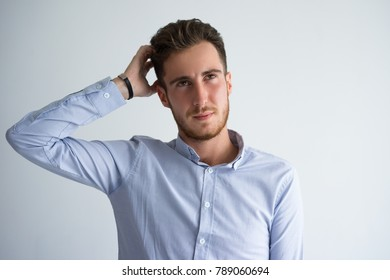 Portrait of confused businessman scratching head