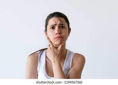 Portrait of confused emotional woman touching chin and thinking. Beautiful frustrated girl looking at camera. Isolated on white. Stress concept