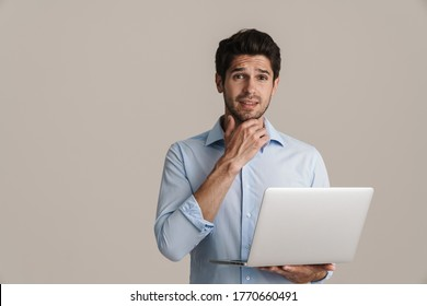 Portrait of confused handsome man looking at camera while using computer isolated over white background
