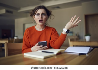 Portrait of confused hipster girl sitting with open mouth disappointed of examination testing receiving feedback on smartphone connected to internet, young student angry about bug in phone application