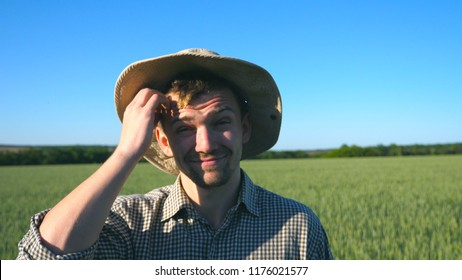 Portrait of confused male farmer looking into the camera and scratching his head. Close up of young doubtful man standing in the meadow on sunny day. Green wheat field under blue sky at background.