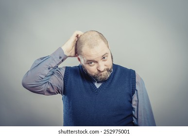 Portrait of a confused male individual with hand in hair