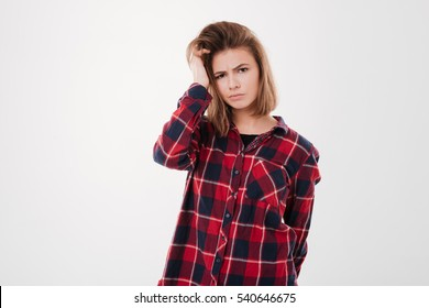 Portrait of a confused pretty girl in plaid shirt looking at camera isolated on a white background