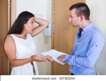 Portrait of confused tenant and furious landlord with unpaid bills in home