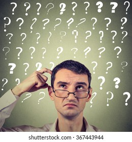 Portrait confused thinking young man in glasses bewildered scratching his head seeks a solution looking up at many question marks isolated on gray wall background. Human face expression