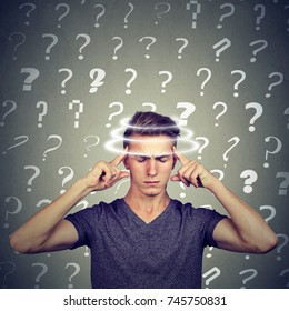 Portrait confused thinking young man with vertigo dizziness has many questions isolated on gray wall background. Human face expression