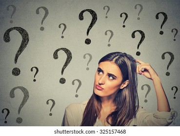 Portrait confused thinking young woman bewildered scratching her head seeks a solution looking up at many question marks isolated on gray wall background. Human face expression