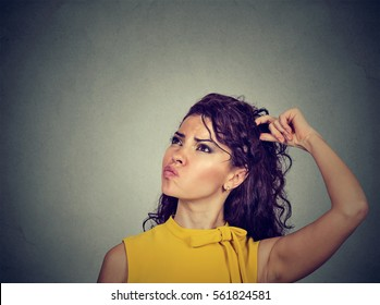 Portrait confused thinking young woman bewildered scratching her head seeks a solution looking up isolated on gray wall background. Human face expression