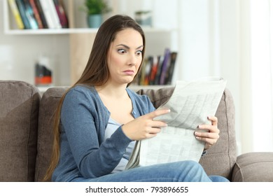 Portrait of a confused woman reading absurd news in a newspaper sitting on a couch in the living room at home