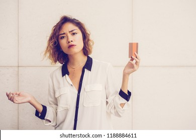 Portrait of confused young Asian woman showing credit card. Cardholder dissatisfied with service. Finance and banking concept