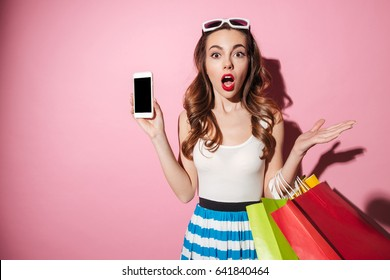 Portrait of a confused young girl with shopping bags showing blank screen mobile phone isolated over pink background