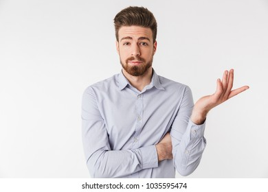 Portrait of a confused young man dressed in shirt looking at camera isolated over white background