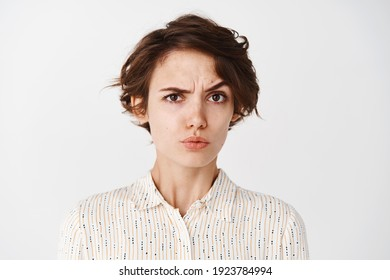 Portrait of confused young woman stare skeptical at camera, raise eyebrow in disbelief, looking at you, standing on white background.