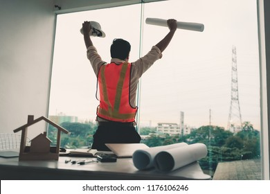 Portrait of construction engineer is looking at site construction through the glass of windows.