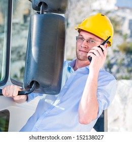 Portrait of construction manager using walkie-talkie near a truck
