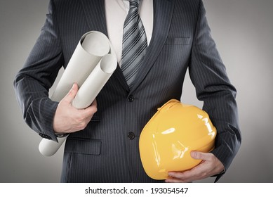 Portrait of construction master holding yellow helmet and blueprint in hands.
