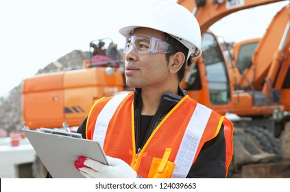 portrait construction worker in front of excavator checking plan