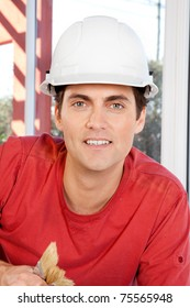 Portrait of a construction worker with paint brushes and white hard hat