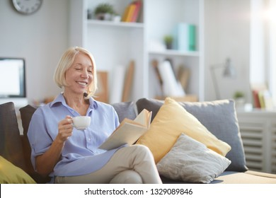 Portrait of contemporary adult woman reading book sitting on sofa at home and smiling happily, copy space