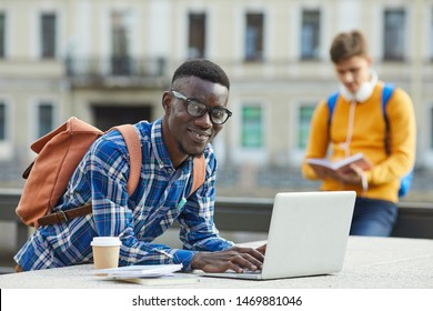 Portrait of contemporary African student using laptop outdoors in college campus, copy space