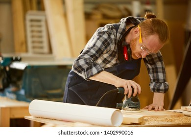 Portrait of contemporary carpenter polishing wood while working in sunlight, copy space