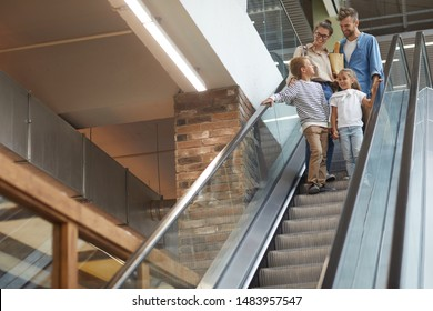 Portrait of contemporary family with two kids going down escalator in shopping mall, copy space