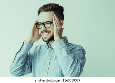 Portrait of content attractive young man posing and using hands as blinders. Businessman surprised with good news and clutching head joyfully. Good news and business success concept.