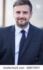 Portrait of content handsome businessman in elegant suit