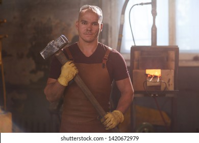 Portrait of content handsome young worker in apron and protective gloves standing against furnace and holding sledgehammer