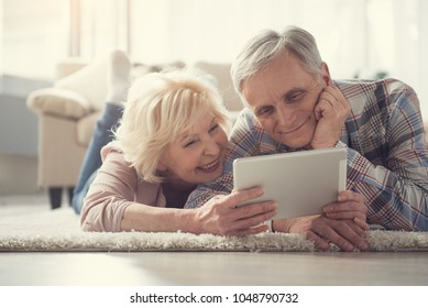 Portrait of content pensioners relaxing on soft rug in living room and looking at tablet