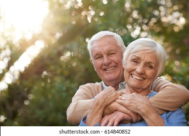 Portrait of a content senior man hugging his smiling wife from behind while standing together outside in their yard on a sunny day