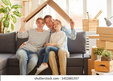 Portrait of content young family in casual clothing sitting on gray sofa and holding cardboard roof above their heads