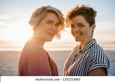Portrait of a content young lesbian couple smiling while standing close together on a sandy beach at sunset