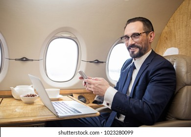 Portrait of contented diplomat sitting at tray table in airplane and holding cellphone in hands, he is looking at camera and smiling