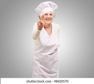 portrait of a cook senior woman doing an approval gesture over a grey background