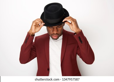 Portrait of cool african american male fashion model posing with hat and blazer by white background