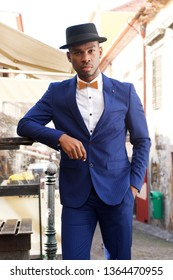 Portrait of cool african american male model posing on city street with suit and bowtie