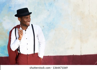 Portrait of cool african american male fashion model smiling with vintage suit, suspenders and hat by wall