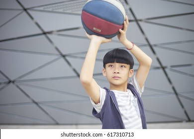 portrait of cool Asian kid holding basketball aiming & shooting