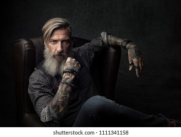 Portrait of a cool bearded businessman, who is sitting on an armchair