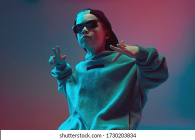 Portrait of a cool boy child in a rap image, stylishly posing in a hoodie, sunglasses and a cap on a neon background.